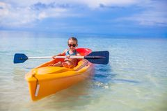 Little adorable girl kayaking in the clear blue Stock Photo