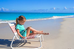 Little adorable girl with laptop on beach during Royalty Free Stock Images