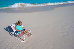 Little adorable girl with laptop on beach during summer vacation Stock Image
