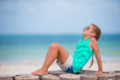 Little adorable girl listening to music on headphones on the beach Stock Image