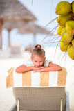 Little adorable girl near coconut on white tropical beach Royalty Free Stock Image