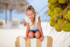Little adorable girl near coconut on white tropical beach Royalty Free Stock Photos