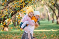 Little adorable girls at warm day in autumn park outdoors stock image