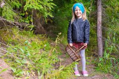 Little adorable girl pick up mushrooms in autumn Stock Photo