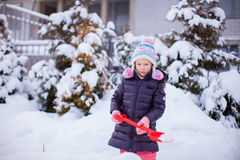 Little adorable girl play with snow shoveling on Stock Photography