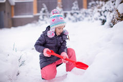 Little adorable girl play with snow shoveling on a Royalty Free Stock Image