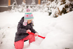 Little adorable girl play with snow shoveling on a Royalty Free Stock Photography