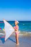 Little adorable girl playing with flying kite on Stock Image