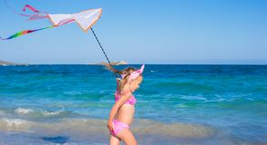 Little adorable girl playing with flying kite on Royalty Free Stock Photo
