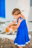 Little adorable girl playing with ginger cat in greek village outdoor Stock Photo