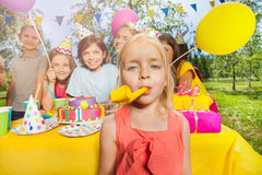 Little adorable girl playing with party blower Royalty Free Stock Photography