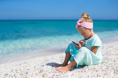 Little adorable girl playing in phone during beach Royalty Free Stock Image