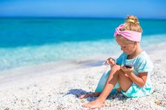 Little adorable girl playing in phone during beach Stock Images