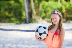 Little adorable girl playing voleyball on beach with ball Royalty Free Stock Image
