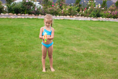 Little adorable girl playing with water gun Royalty Free Stock Image