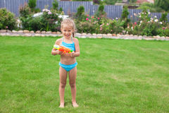 Little adorable girl playing with water gun Royalty Free Stock Images