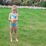 Little adorable girl playing with water gun. Outdoor in sunny summer day. This image has attached release stock photos