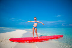 Free Little Adorable Girl Practice Surfing Position At Royalty Free Stock Photos - 53889718