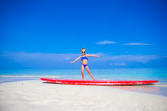 Little adorable girl practice surfing position at Royalty Free Stock Photos