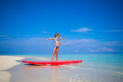 Little adorable girl practice surfing position at Stock Image