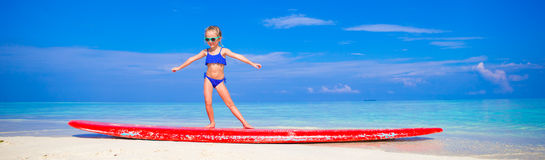 Little adorable girl practice surfing position at Stock Photography
