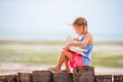 Little adorable girl reading book during tropical white beach Stock Photos