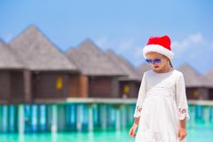 Little adorable girl in red Santa hat on the beach Stock Photography