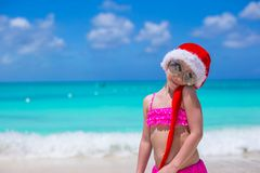 Little adorable girl in red Santa Hat on tropical Stock Images