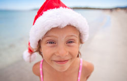 Little adorable girl in red Santa hat at tropical Stock Photography