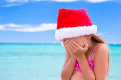 Little adorable girl in red Santa hat at tropical Stock Photo