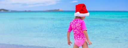 Little adorable girl in red Santa hat at tropical Stock Photos