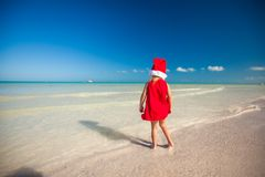 Little adorable girl in red Santa hat at tropical Stock Images