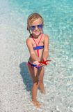 Little adorable girl with sea star at the tropical Royalty Free Stock Images
