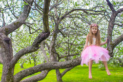 Little adorable girl sitting on blossoming apple Stock Image