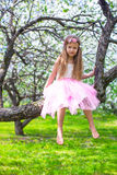 Little adorable girl sitting on blossoming tree in Royalty Free Stock Photo