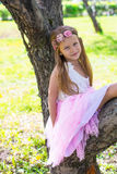 Little adorable girl sitting on blossoming tree in Stock Photo