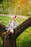 Little adorable girl sitting on blossoming tree in Stock Photography
