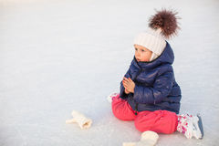 Little adorable girl sitting on ice with skates Stock Photos