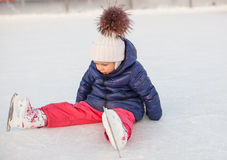 Little adorable girl sitting on ice with skates Royalty Free Stock Photo