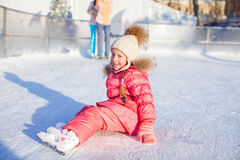 Little adorable girl sitting on ice with skates Royalty Free Stock Image