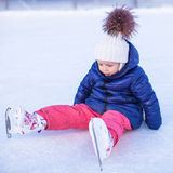 Little adorable girl sitting on ice with skates Stock Photography