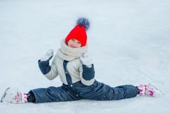 Little adorable girl sitting on ice with skates after fall Stock Photo