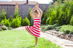 Little adorable girl standing in a yoga pose on Stock Images