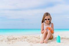 Little adorable girl with suncream bottle on the beach Stock Photo