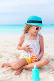 Little adorable girl with suncream bottle on the beach Royalty Free Stock Photos