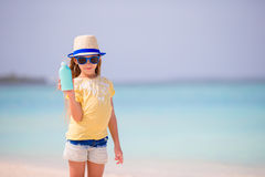 Little adorable girl with suntan lotion bottle on the beach Stock Image