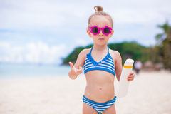 Little adorable girl with suntan lotion bottle on Stock Images
