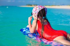 Little adorable girl on a surfboard in the Stock Images