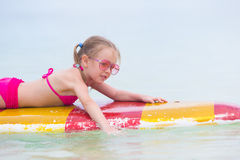 Little adorable girl on a surfboard in the Stock Photo