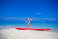Little adorable girl on a surfboard in the Stock Image